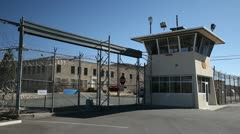 Generic prison gates with guard tower on sunny day two, 973  Stock Footage