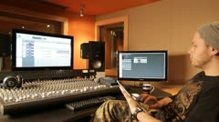 Musical producer working with tablet in recording studio - tracking shot - stock footage