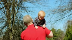 Grandfather playing with infant granddaughter walking Stock Footage