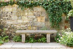 bench in formal garden - stock photo