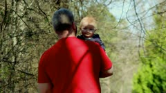 Grandfather walking with infant granddaughter smiling Stock Footage