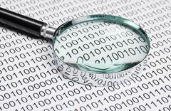Magnifying glass on a binary code Stock Photos