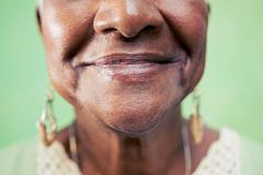 Old black woman portrait, close-up of eye and face on green background. copy Stock Photos