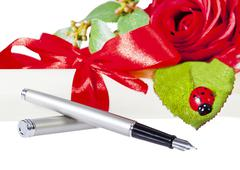 fountain pen owith rose lady bug and parchment - stock photo