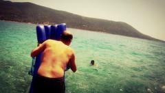 Funny dive of a man holding a sea mattress, into the sea, instagram look - stock footage