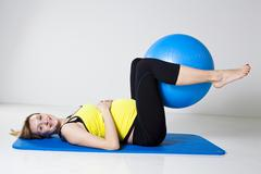 pregnant woman exercising with fitness ball - stock photo