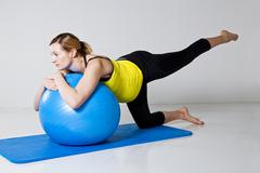 Pregnant woman exercising with fitness ball Stock Photos