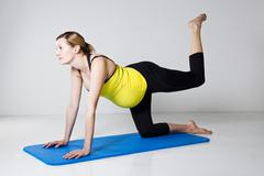 pregnant woman exercising on mat - stock photo