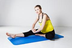 Pregnant woman performing leg stretch Stock Photos