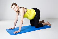pregnant woman kneeling on mat - stock photo