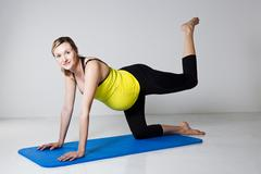 pregnant woman exercising on mat - stock photo