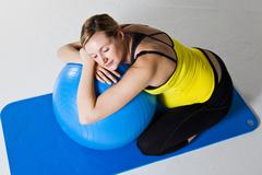 pregnant woman relaxing against fitness ball - stock photo