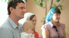 Family with a baby on the baptism in the church Stock Footage