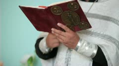 Priest with Bible in hands - stock footage
