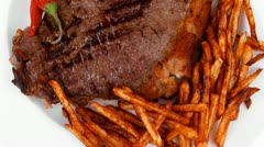 Entree : grill beef meat steak on white round plate with dry hot chili pepper Stock Footage