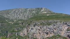 Pan limestone rocks tilt down Gorge du Verdon + flowing river Stock Footage