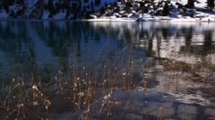 Small pieces of ice on the dried grass against the mountain lake Stock Footage