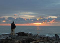 A fisherman at the dusk Stock Photos
