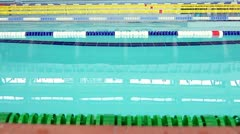 Swimming pool with blue water, underwater swimmers on blue background Stock Footage
