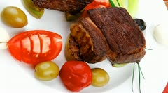 Grilled meat : beef ( lamb ) garnished with tomatoes green and black olives Stock Footage