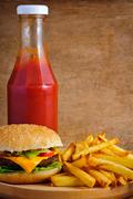 Cheeseburger, fries and ketchup Stock Photos