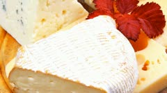 Edam parmesan and brie cheese on wooden platter over wooden table Stock Footage