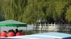People boating on lake relying on China Beijing Beihai Park willow island. Stock Footage