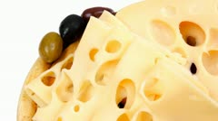 Gold edam cheese sliced on wooden platter with olives and tomato Stock Footage