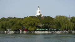 China Beijing ancient architecture Beihai Park white tower on willow island. Stock Footage