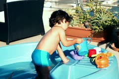 Little boy playing with bucket in paddling pool, slow motion shot at 120fps Stock Footage