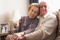 Loving Senior Couple Relaxing At Home Stock Photos