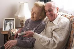 Senior Couple Watching TV At Home Stock Photos