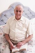 Senior Man Reading Book On Bed Stock Photos