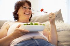 Overweight Woman Relaxing On Sofa - stock photo