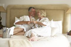 Middle Aged Couple Enjoying Champagne In Bedroom Stock Photos