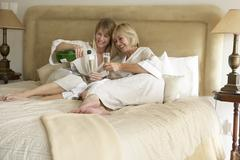 Two Women Enjoying Champagne In Bedroom - stock photo