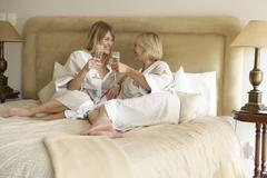 Two Women Enjoying Champagne In Bedroom Stock Photos