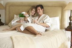 Young Couple Enjoying Champagne In Bedroom Stock Photos