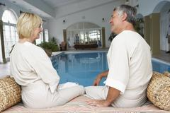 Middle Aged Couple Relaxing By Swimming Pool Stock Photos