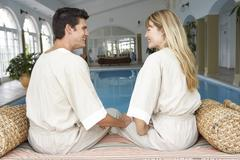 Young Couple Relaxing By Swimming Pool Stock Photos