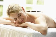 Stock Photo of Young Woman Enjoying Hot Stone Treatment
