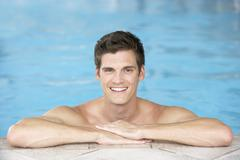 Young Man Resting On Edge Of Swimming Pool Stock Photos