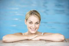 Young Woman Resting On Edge Of Swimming Pool Stock Photos