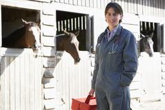 Portrait Of Vet Standing By Horse Stables Stock Photos