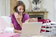 Woman using laptop and talking on phone Stock Photos