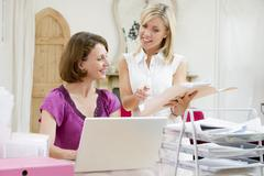 Women looking at paperwork together Stock Photos