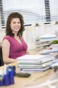 Woman sitting happily at her desk - stock photo