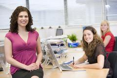 Women happily working in an office - stock photo
