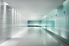Back-lighted glass walls in an underground futuristic corridor Stock Photos