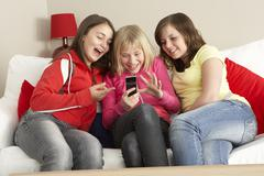 Group Of Three Girls Reading Text Message Stock Photos